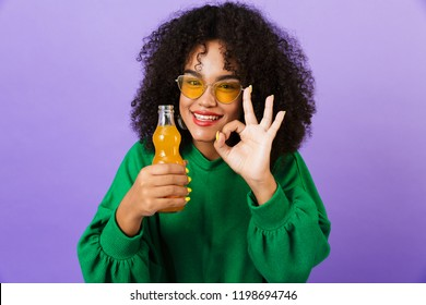 Image of amazing pretty african woman isolated over violet background showing okay gesture drinking soda.