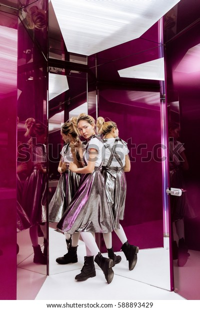 Image of amazing young asian woman posing over mirror labyrinth. Looking aside.