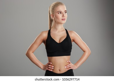 Image of amazing young blonde sports lady standing isolated over grey wall background. Looking aside.