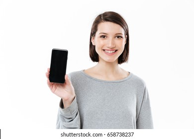 Image of amazing young caucasian woman standing isolated over white wall. Looking at camera showing display of phone.