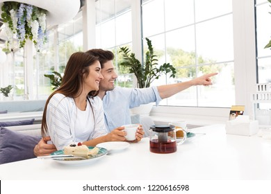 Image of amazing young loving couple sitting in cafe eat desserts and drinking tea looking aside pointing.