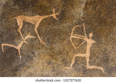 The image of an ancient hunter and animals on the wall of the cave. history of antiquities. archaeology.