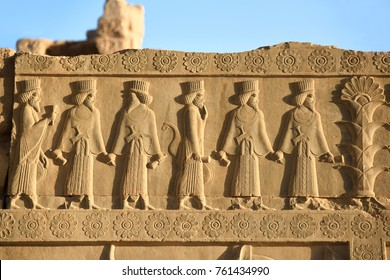 Image of ancient Persian ambassadors. Bearded men facing each other and holding hands. An ancient relief on the walls of the ruined city of Persepolis. Persepolis. Iran.