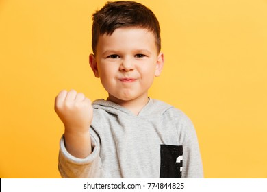 Image of angry little boy child standing isolated over yellow background. Looking camera gesturing with hand.