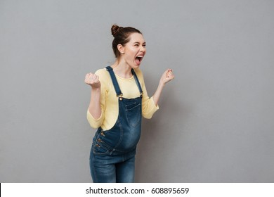 Image of angry screaming pregnant woman posing isolated over grey wall.