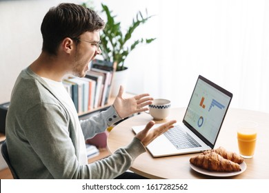 Image of angry young man in eyeglasses screaming and looking at screen while working on laptop at home