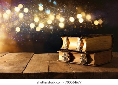 Image of antique books, with brass clasps on old wooden table. fantasy medieval period and religious concept. Glitter overlay