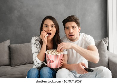 Image of anxious family sitting on sofa at home and looking at you while watching scary movie and eating popcorn