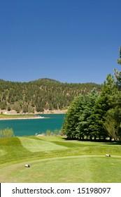 An image of a aqua lake set near a golf hole