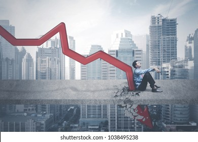 Image of Arabian businessman looks tired while sitting near declining arrow on the bridge
