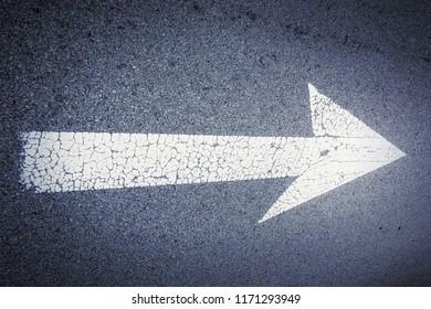 an image of an arrow sign on asphalt road
