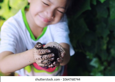 Image of Asian 5 years old girl learn to planting.Girl hold soil on hands and smile.Happy nature classroom from backyard.Concept of nature and outdoor education,independence and self-esteem kid.