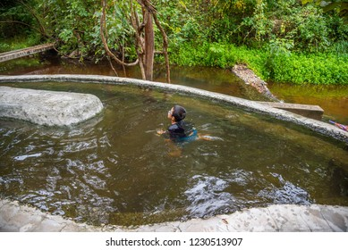 Image of Asian boy swimming in hot spring pond at Pong Nam Ron Tha Pai the famous attraction lanmark at Pai district, Mae Hong Son ,Thailand.