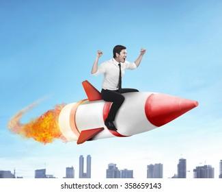 Image of asian business man flying ride rocket