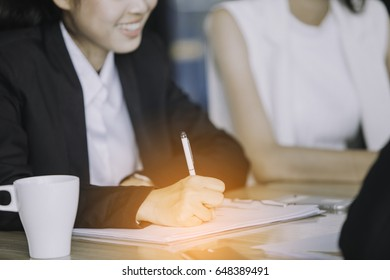 Image of Asian business partners discussing documents and ideas at meeting. ,Group of business people busy discussing financial matter during meeting.,training business concept