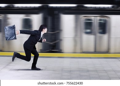 Image of Asian businessman carrying a suitcase while rushing for a train with fast motion blur