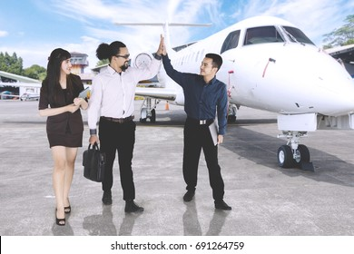 Image of Asian businessman giving high five with his friends while standing near the airplane