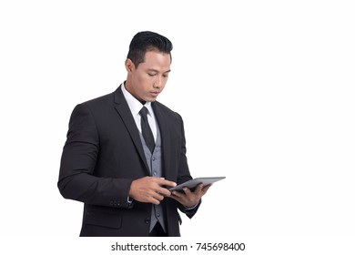 Image of Asian businessman is looking at his digital tablet while standing over white wall background isolated /Modern life concept