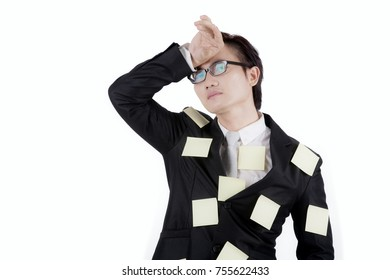 Image of Asian businessman looks tired while standing with sticky notes on his body, isolated on white background