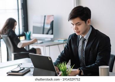 Imagen de un empresario asiático estudiando y analizando su trabajo usando una tableta en la oficina.