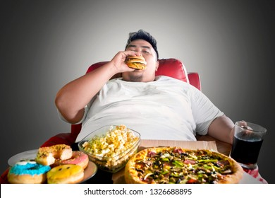 Image of Asian fat man looks greedy while eating junk foods on the sofa. Shot in the dark room