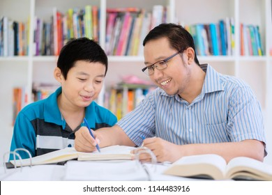Image of Asian male teacher helping his student to read a book while sitting in the library