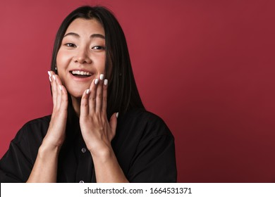 Image of an asian surprised optimistic happy young woman posing isolated over red wall background.