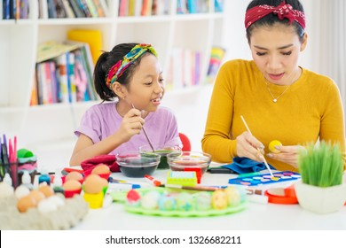 Image of Asian woman and her daughter decorating Easter eggs with liquid dye at home