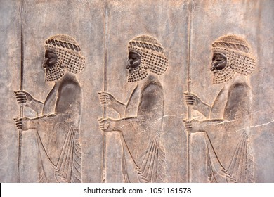 Image of assyrian warriors with spears in their hands. Ancient reliefs on the ruined walls of the Persepolis. Persepolis. Iran.