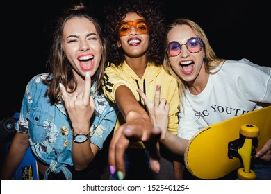 Image of astonished multinational girls in streetwear smiling and holding skateboards at night walk outdoors