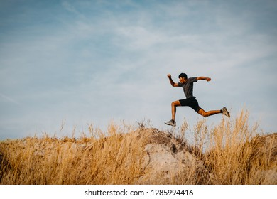 Image of Athlete trail running, runner running on hill.