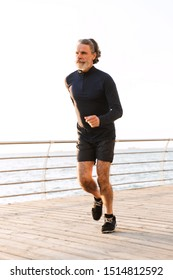 Image of athletic old man in tracksuit running while working out near seaside in morning