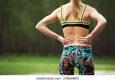 Image of athletic young woman rubbing the muscles of her lower back after jogging in park