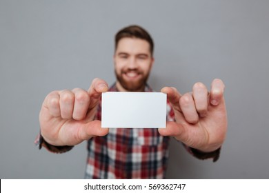 Image of attractive bearded man showing copyspace business card to camera. Focus on card.