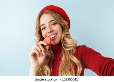 18005c79 Image of attractive blond woman 20s wearing red beret eating macaron  biscuit while taking selfie photo