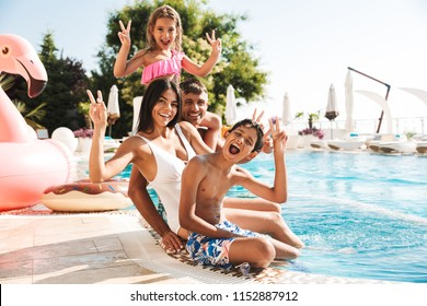 Image of attractive caucasian family with children sitting near luxury swimming pool with pink rubber ring outside hotel