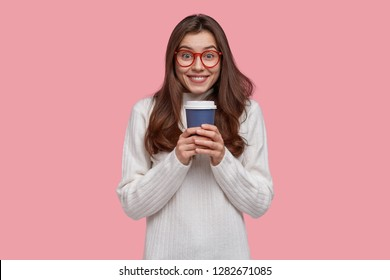 Image of attractive dark haired lady holds takeaway coffee or tea, enjoys spare time, wears white loose sweater, poses over pink background. Satisfied youngster drinks hot aromatic beverage indoor.