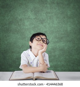 Image of an attractive elementary school student daydreaming in the classroom with a book on the table and wearing glasses