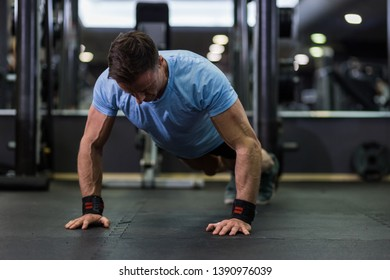 Image of an attractive man doing push-up at the gym.