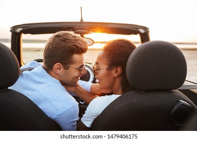 Image of attractive multiethnic couple man and woman kissing while siting in convertible stylish car by seaside at sunset