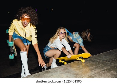 Image of attractive multiethnic girls in streetwear smiling and riding skateboards at night outdoors