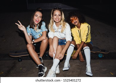 Image of attractive multinational girls in streetwear smiling and sitting on skateboards at night party outdoors