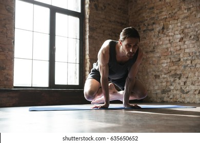 Image of attractive strong sportsman in gym make yoga sport exercises. Looking aside.