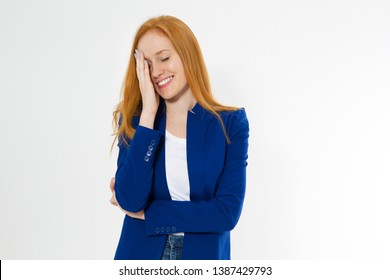 Image of attractive stylish red hair woman in blue style suit making facepalm, holding hand on eye and smiling, coming to terms with stupid sense of humour of boyfriend
