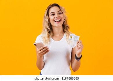 Image of attractive woman holding cell phone and credit card in hands isolated over yellow background