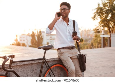 Image of attractive young african man early morning with bicycle outdoors. Looking aside talking by phone.