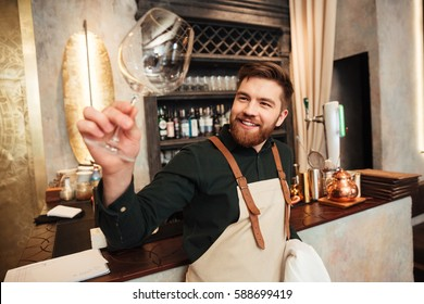 Image of attractive young bearded man bartender standing in cafe. Looking aside and wipe the glass.