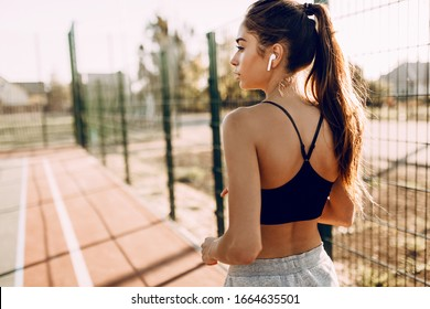 Image of attractive young fitness girl running, outdoors and listening to music with headphones, morning jog