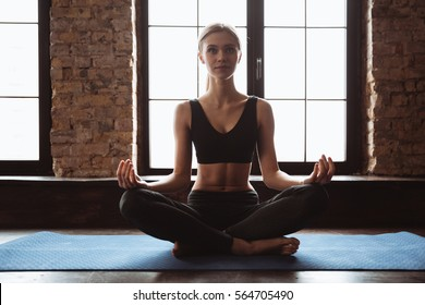 Image of attractive young fitness lady sitting in gym near window while make yoga exercises.