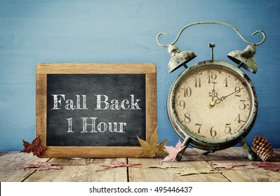 Image of autumn Time Change. Fall back concept. Dry leaves and vintage alarm Clock on  rustic wooden table